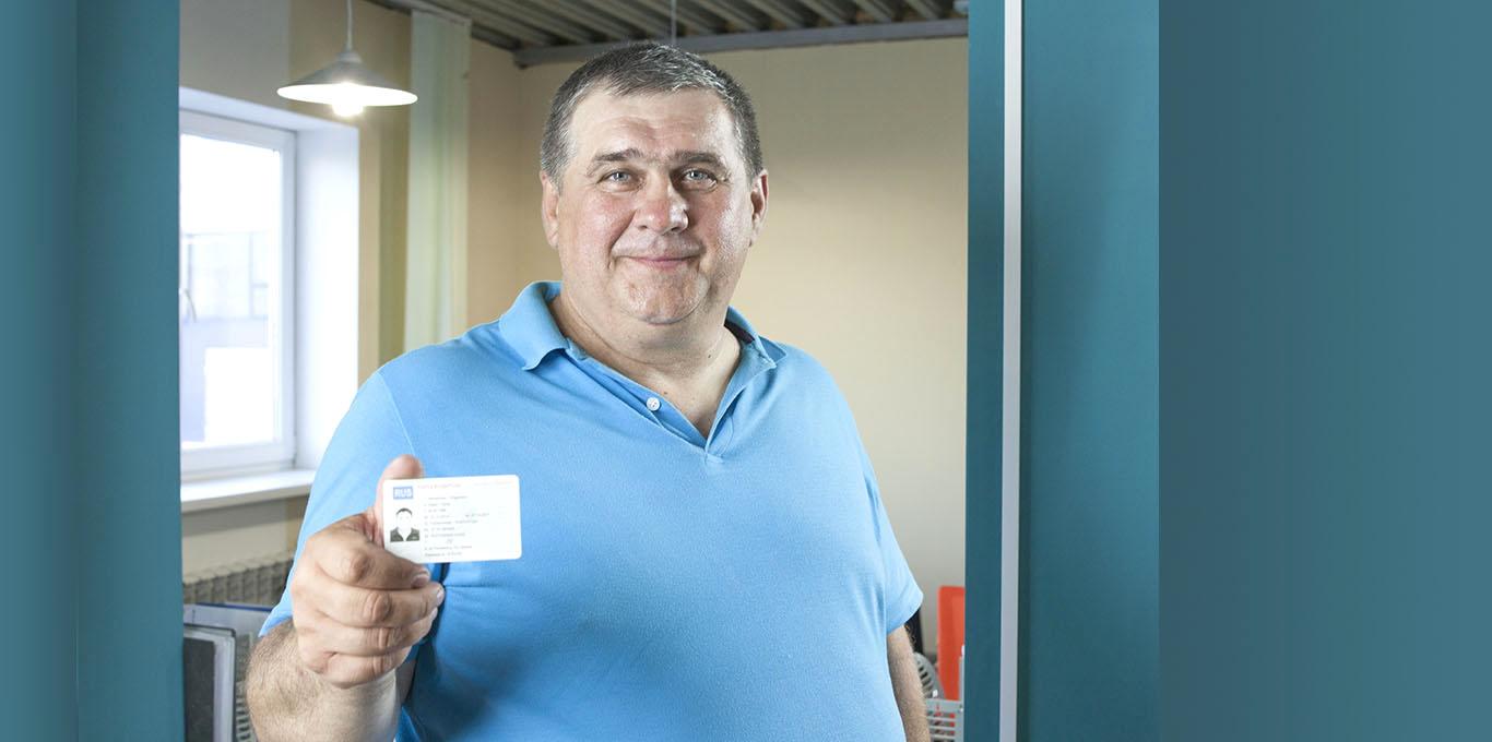 Водитель держит в руке карту водителя для тахографа